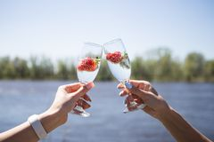 Two female hands holding a glass of champagne with strawberries. Background river stock images