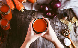 Two female hands holding an iron mug with carrot juice Stock Photography