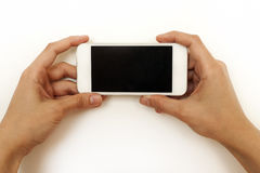 Two female hands holding mobile phone, smartphone. On white Royalty Free Stock Photos