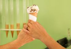 Two female hands holding a vanilla with chocolate ice cream cone. Woman sells ice cream in pastry shop. Two female hands holding a vanilla with chocolate ice Royalty Free Stock Photos