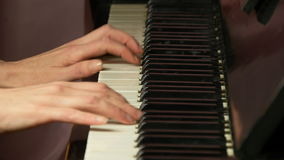 Two female hands playing a gentle piece of classical music on a beautiful grand piano. Woman playing the piano, close-up.  stock video