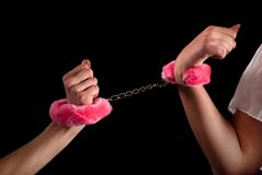 Two female hands tied with handcuffs. Two Couple Young women hands in handcuffs with pink fur puffy. Close up. Seductive love concept Royalty Free Stock Images
