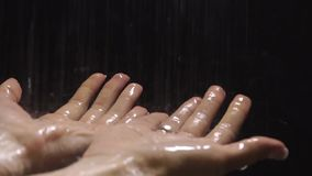 Two female hands under the shower with black background, slow motion video. Clip stock footage