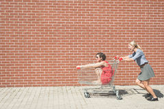 Two female having fun with a shopping cart at the mall parking lot Royalty Free Stock Photos