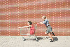 Two female having fun with a shopping cart at the mall parking lot Royalty Free Stock Photography