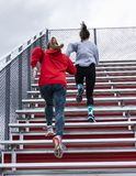 Two female high school athletes running up bleachers stock images