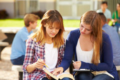 Two Female High School Students Working On Campus. Close Up Of Two Female High School Students Working On Campus Reading Textbook Royalty Free Stock Image