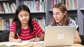 Two female high school students working at laptop