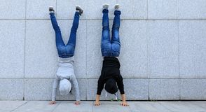 Hipsters doing handstand against wall in city Royalty Free Stock Photography