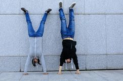 Hipsters doing handstand against wall in city Stock Image