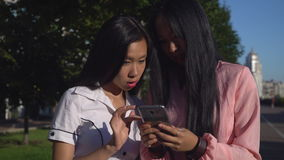 Two female holding cell chatting smiling. Two asian young women using smartphone in the city. Attractive girls looking photo on mobile phone. Beautiful friends stock footage