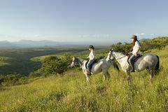 Two female horseback riders on horseback ride at sunset as one points overlooking the valley of Lewa Wildlife Conservancy in North Stock Image