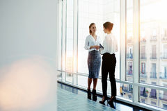 Two female intelligent managers discussed plan the future conference while standing near big office window Royalty Free Stock Image