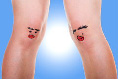 Two female legs with funny faces Stock Images