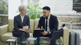 Two female and male business colleagues with clipboard and notepad talking at hotel lobby. Luggage in near couch. Two female and male business colleagues with stock video footage