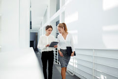 Two female managing directors discussing ideas of project on digital tablet while walking down in office hall, Royalty Free Stock Images
