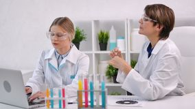 Two female medical scientist working with colorful liquid substance in tube using laptop pc. Medium shot. Woman chemist in uniform analysing reagent making stock video