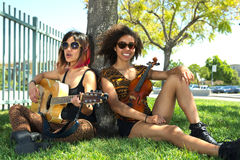 Two female musicians sitting by tree playing music Royalty Free Stock Images