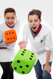 Two female nurses rolling dices Stock Images