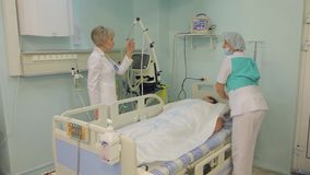 Two Female nurses visit the patient and discuss his condition. A female nurse visits a patient. A woman doctor approaches her and they discuss the condition of stock video footage