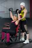 Two female partners train in gym with dumbbells Stock Photography