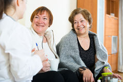 Two female pensioners discussing health problems with doctor Royalty Free Stock Image