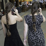 Two young women with ponytails talking on the phon. Two women with ponytails walking and talking on the phone stock photography