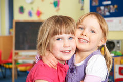 Two Female Pre School Pupils Hugging One Another Stock Images