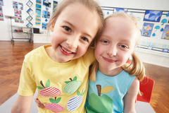 Two Female Primary Schoolchildren In Classroom Stock Photo