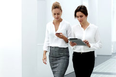 Two female professional staff using smart phone and touch pad while walking in modern office interior, Royalty Free Stock Photography