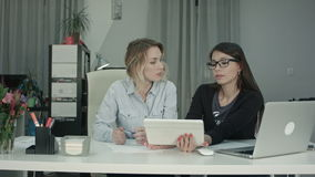 Two female professionals using digital tablet while working at the desk. Professional shot on BMCC RAW with high dynamic range. You can use it e.g. in your stock video