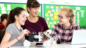 Teacher Talks To Pupils Building Robotic Car In Science Lesson. Two female pupils building model robotic car are joined by their female teacher who discusses the stock video