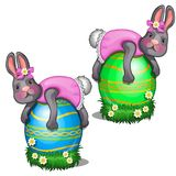 Two female rabbits in pink dress lie on large colorful Easter eggs. Holiday symbol. Vector isolated on white. Two female rabbits in pink dress lie on large Stock Image