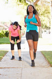 Two Female Runners Exercising On Suburban Street Royalty Free Stock Photo