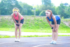 Two Female Runners Standing on Lines Prior to Training Start off. Jogging and Fitness Concepts. Two Female Runners Standing on Lines Prior to Training Start off Royalty Free Stock Photography