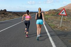 Two female running athletes. Women trail runner sprinting for success goals and healthy lifestyle in amazing nature landscape stock photography