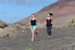 Two female running athletes. Royalty Free Stock Images