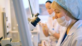 Two female scientists are working in a laboratory with medical equipment. stock video