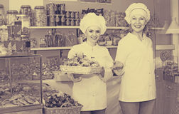 Two female sellers in confectionery. Portrait of two friendly women at confectionery display with pastry. Focus on left woman Royalty Free Stock Photos
