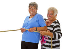 Two female seniors pulling on a rope Stock Images