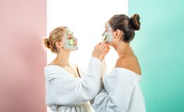 Two female sisters have weekend at bedroom. Conception of skin care by using fresh cucumber rings and white mask on the. Face royalty free stock image