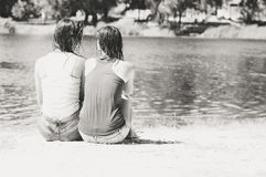 Two female sitting back to camera on summer beach Royalty Free Stock Photography