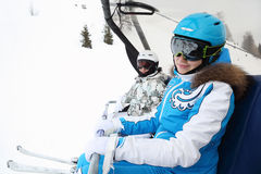 Two female skiers ride on cable car Stock Photos