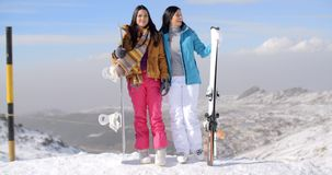 Two female snowboarders standing on a mountain. Two female snowboarders standing side by side in the sunshine on a mountain summit at the edge of a ski run stock video footage