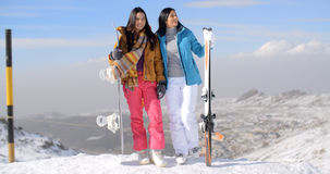 Two female snowboarders standing on a mountain Stock Images