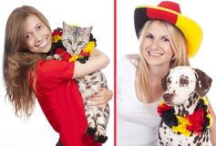 Two female soccer fans with cat and dog Royalty Free Stock Photo