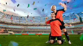 Two female soccer players celebrating victory on full stadium Stock Photo