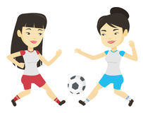 Two female soccer players fighting for ball. Two asian soccer players fighting over control of ball during a football match. Football players in action during Stock Photo