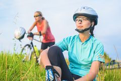 Two female sport athletes resting together outdoors. Royalty Free Stock Photography