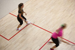 Two female squash players in fast action on a squash court Royalty Free Stock Image